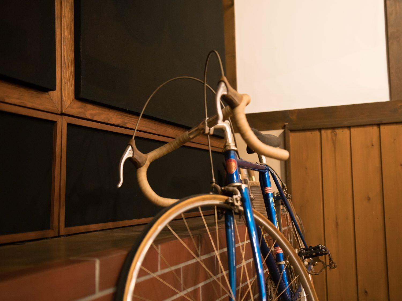 壁に立てかけられている「パブロ」のオーナー村上さんの青い自転車