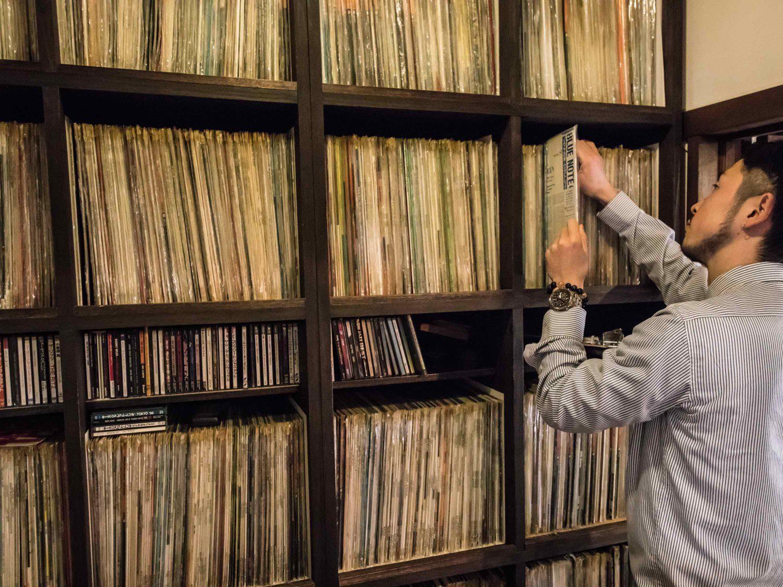 店内のぎっしりと並んでいるレコードから1枚手に取るオーナーの村上さん