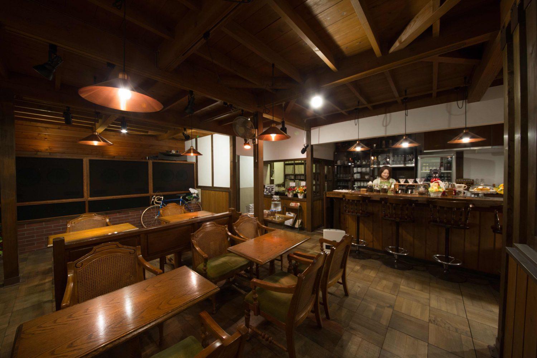 名取のジャズ喫茶「パブロ」の店内の様子。木の雰囲気を生かした建物。奥には木のカウンター席と、手前には木のテーブルと椅子が並ぶ