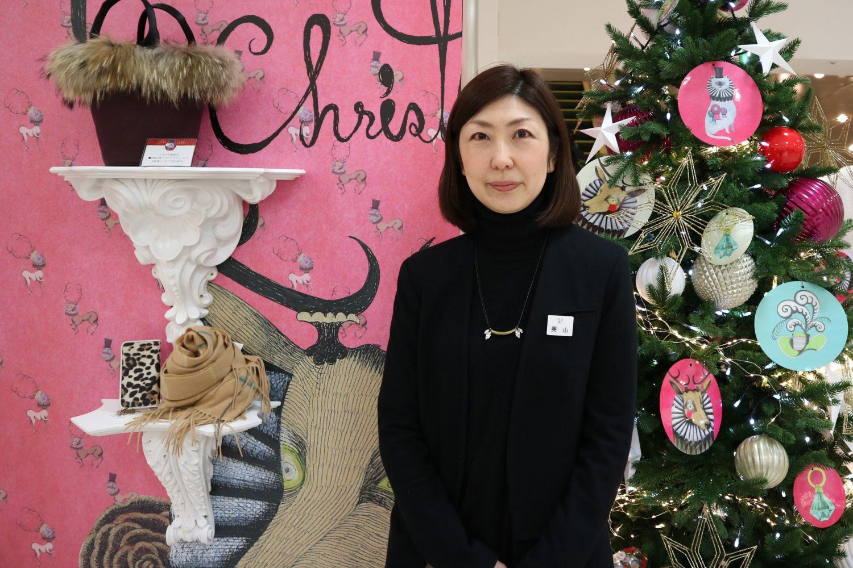 クリスマスツリーやディスプレーをバックに奥山さんの写真