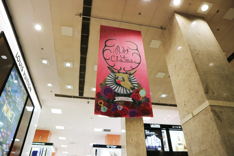 藤崎店内に掲げられたイラスト。ピンクの背景にトナカイが映えている