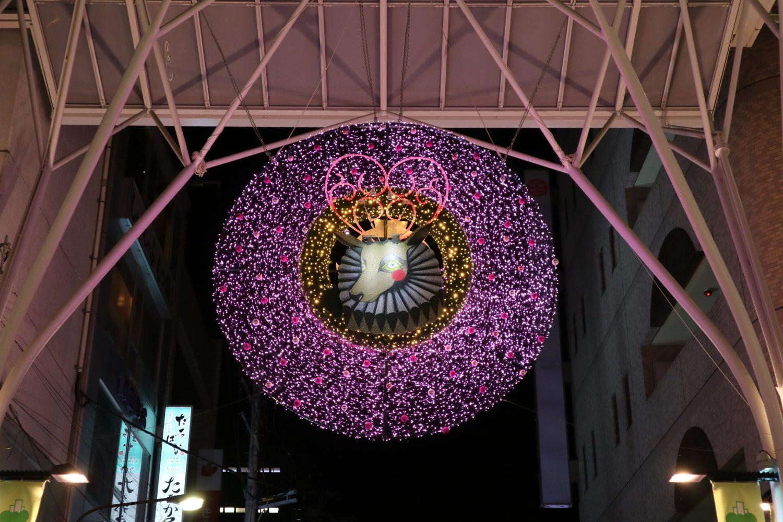 ピンクにライトアップされたリースの真ん中には松下さち子さんのトナカイのイラスト。マーブルロードおおまち商店街に掲げられた