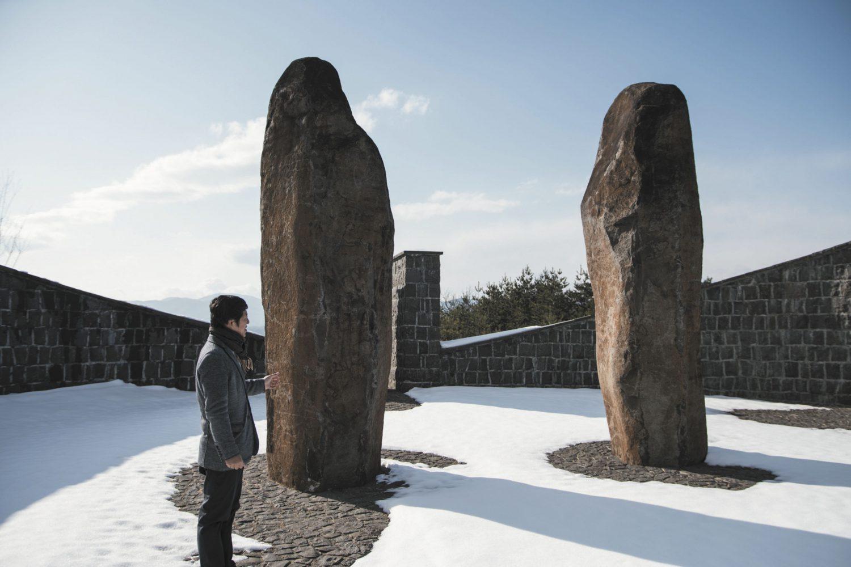 雪が降り積もる中で伊達冠石の巨大な石柱に立つ山田さん