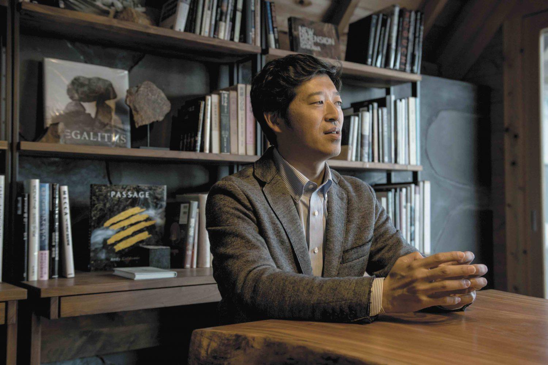 インタビューにこたえる代表取締役・山田能資さん。後ろの本棚には石に関する本が並んでいる