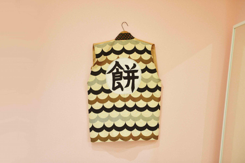 菜美さんが制作したベストの背面。背中には「餅」の文字。使用済みの米の袋を裁断し、仕立てた