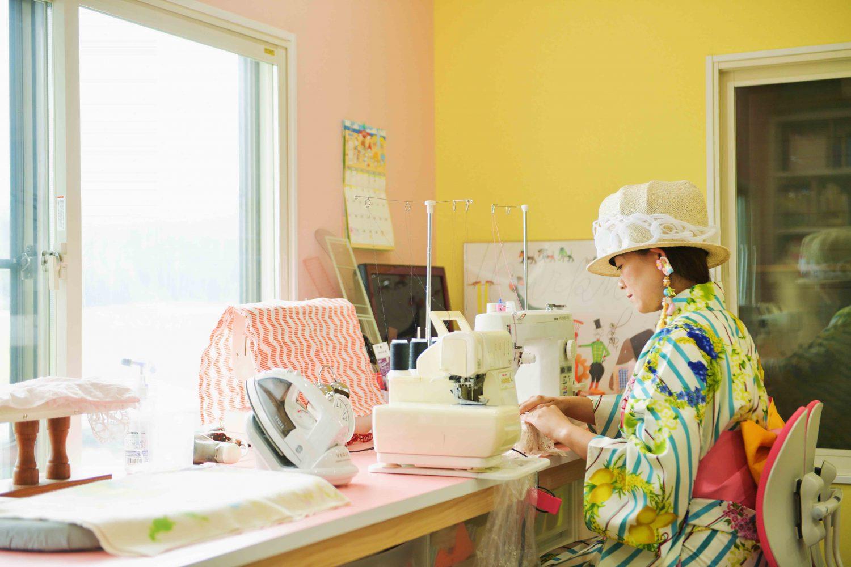 佐藤菜美さんの作業風景。黄色とピンクの壁で白いミシンを扱う菜美さん
