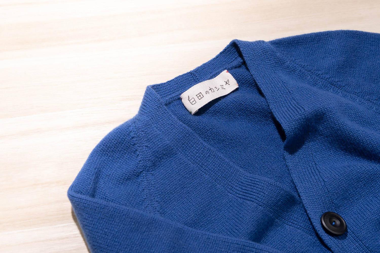「白田のカシミヤ」の首元のタグがかわいい鮮やかな青のカーディガン