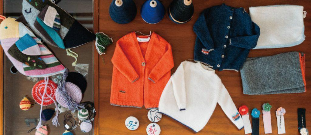 ニットを編む糸や「白田のカシミヤ」の小物、オレンジが鮮やかなカーディガンや白のニットがテーブルに置かれた様子