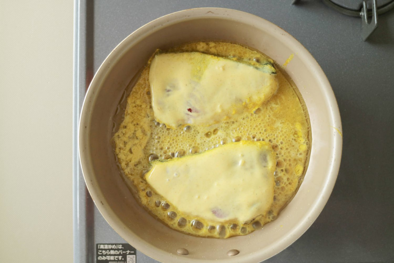 漬け込んだブリ2切れをフライパンで焼いている様子