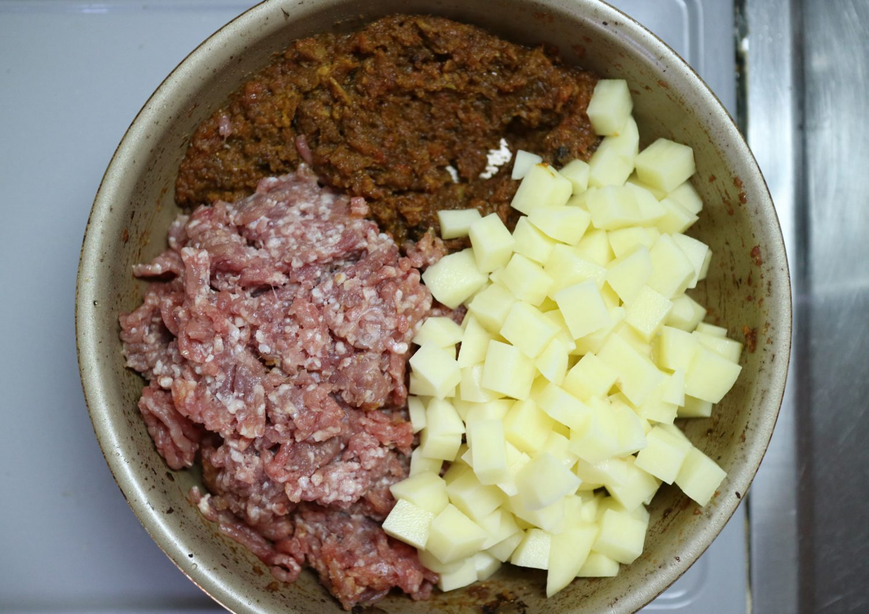 フライパンに新ジャガイモと豚ひき肉を加えた様子