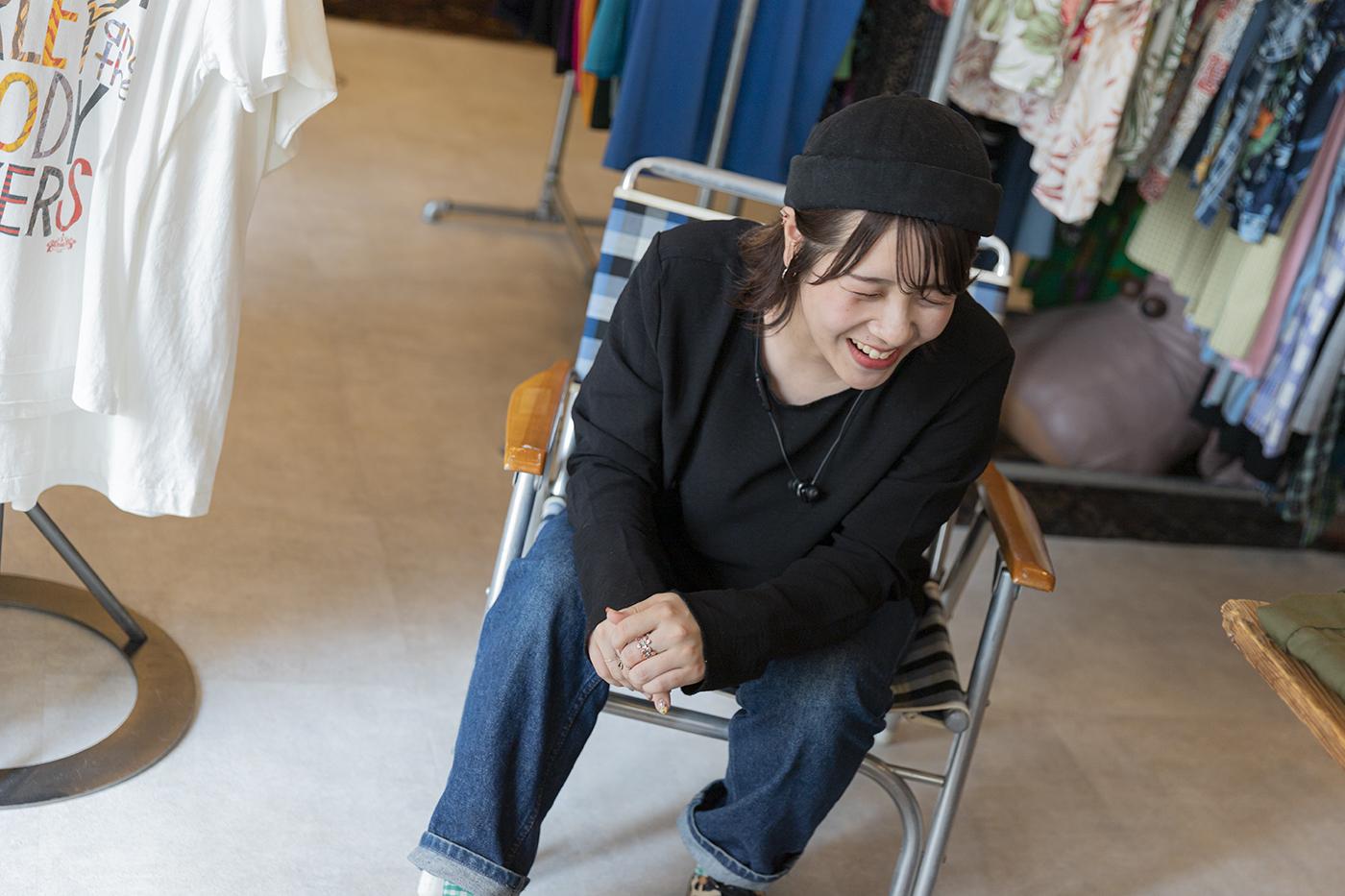 少し伏し目がちな椅子に座った亀井桃さんの写真