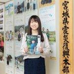宮城県震災復興課の前で広報紙の『NOW IS』を手にする菊池さん