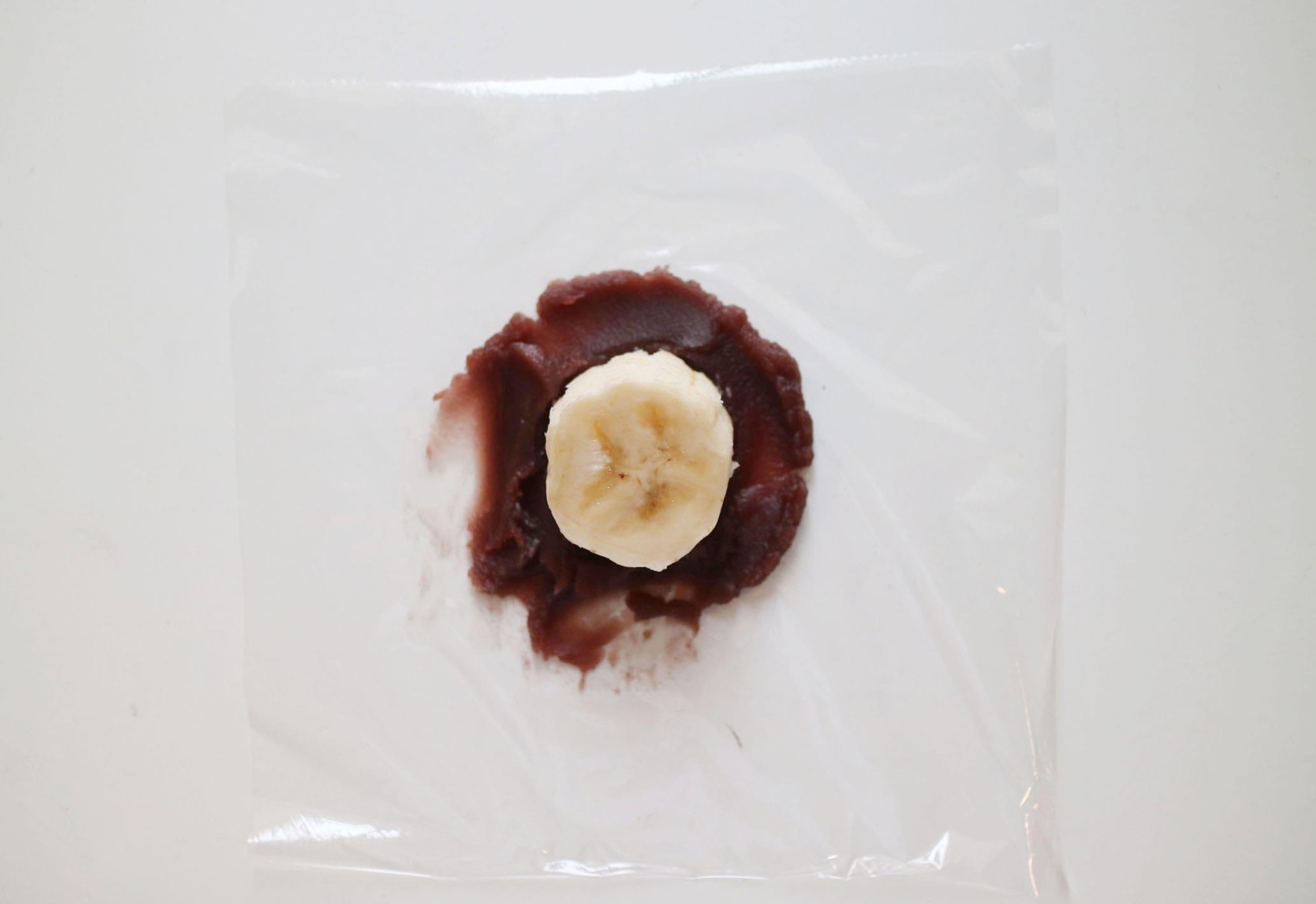 「シナモンバナナ大福の作り方」ラップの上にあんこをのばし、上に切ったバナナが置いてある