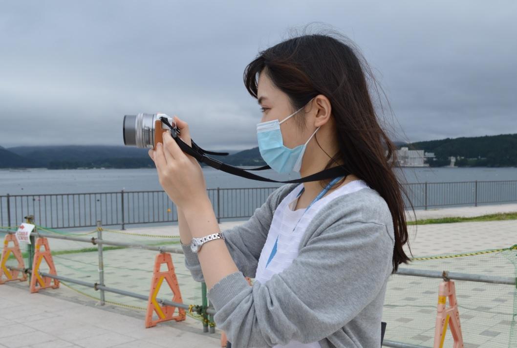 海を背景にカメラを構える菊池さんの横顔