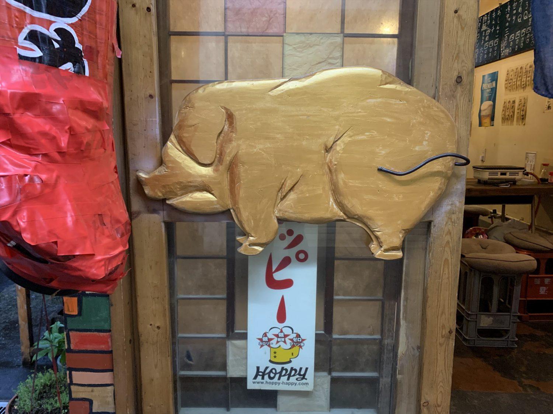 焼肉ホルモン「ブーチャン」の店先には木彫りで金色の豚が飾られてある