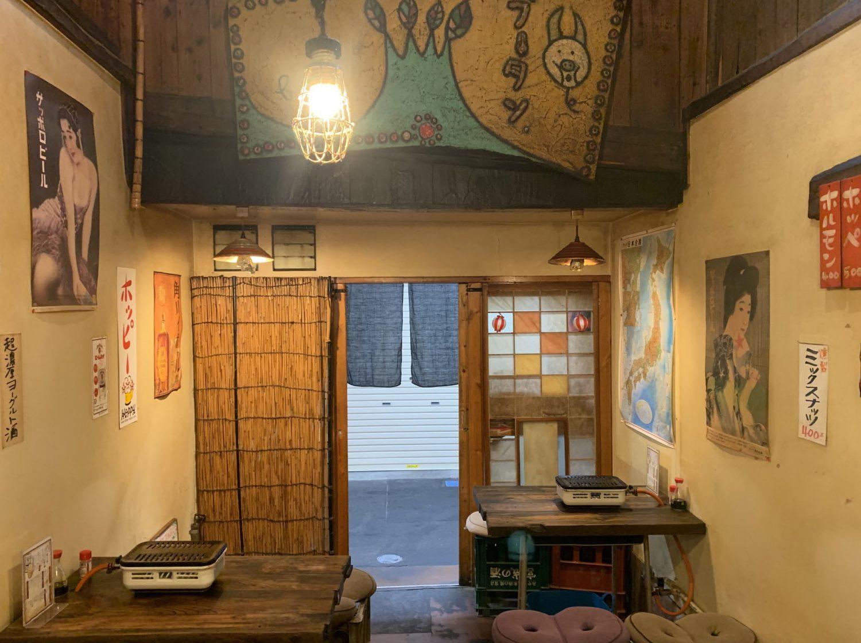 壱二参(いろは)横丁にある焼肉ホルモン「ブーチャン」の店内の様子。懐かしい雰囲気のあるビールのポスターが壁に貼られてある