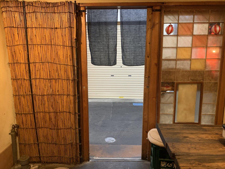 壱二参(いろは)横丁にある焼肉ホルモン「ブーチャン」の店内からみた入口には黒の暖簾が掛けられている