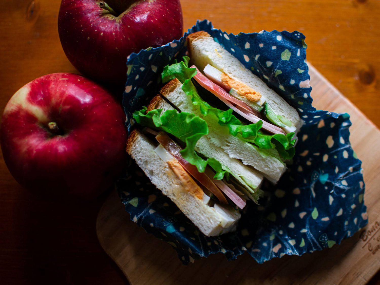 青地のミツロウラップに包まれたサンドイッチ