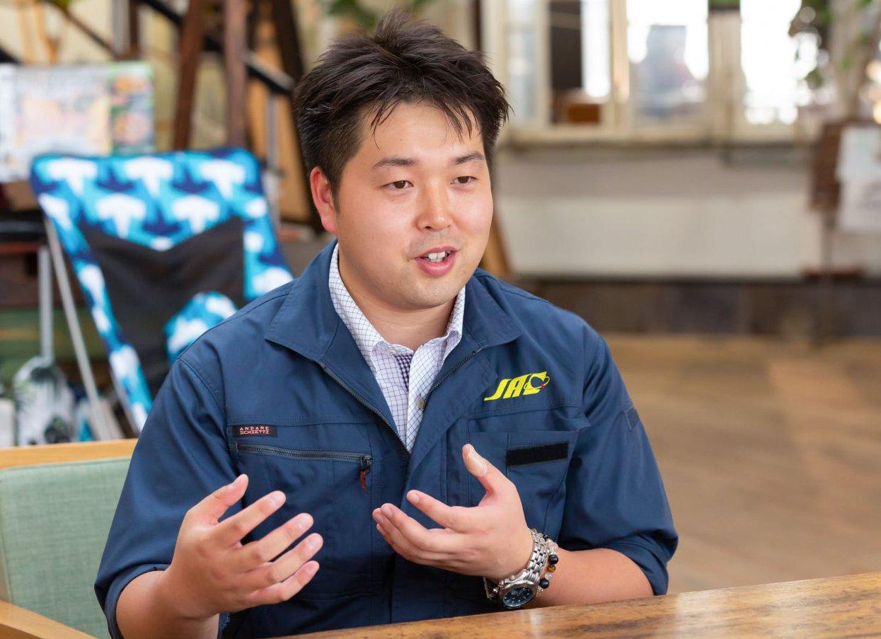 インタビューにこたえる紺色のJACの作業服を着た代表取締役社長の真野仁希さん。