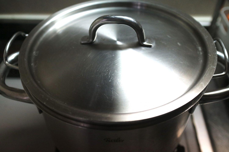炊きあがった米をざる事鍋に入れフタをした様子。炊き上がった米を蒸らしている