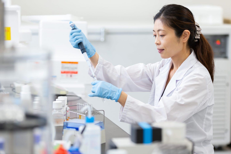 研究室内で白衣を着て作業を行うゼライスの徳田礼枝さん