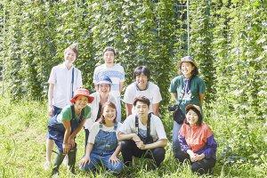 青々としたホップ畑の前でイシノマキ・ファームのメンバーの皆さんの集合写真