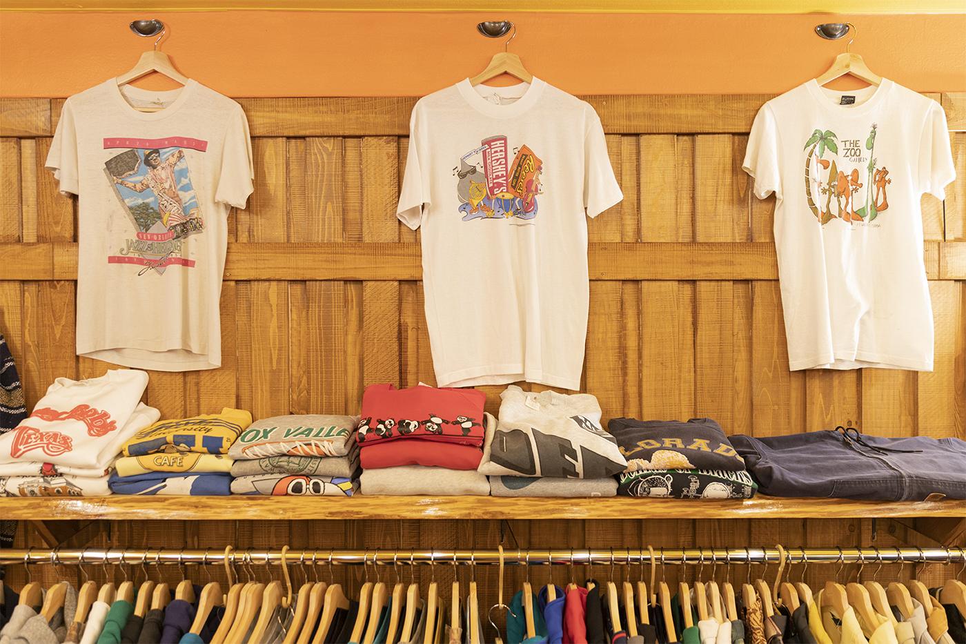 古着屋「chuple」のラックと、壁に掛けられたデザイン白Tシャツ
