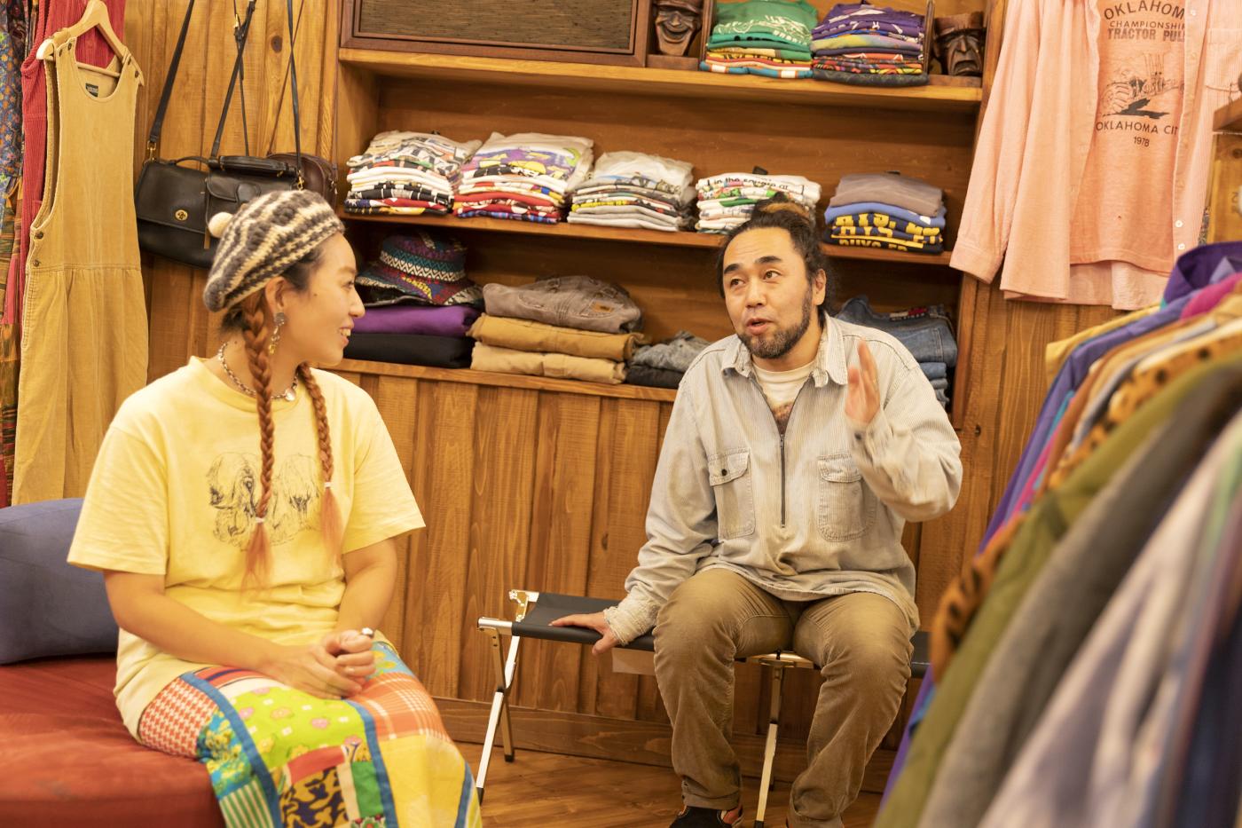 古着屋「chuple」のカツゲンさんがインタビューにこたえる様子。メグミさんがそれを見つめる
