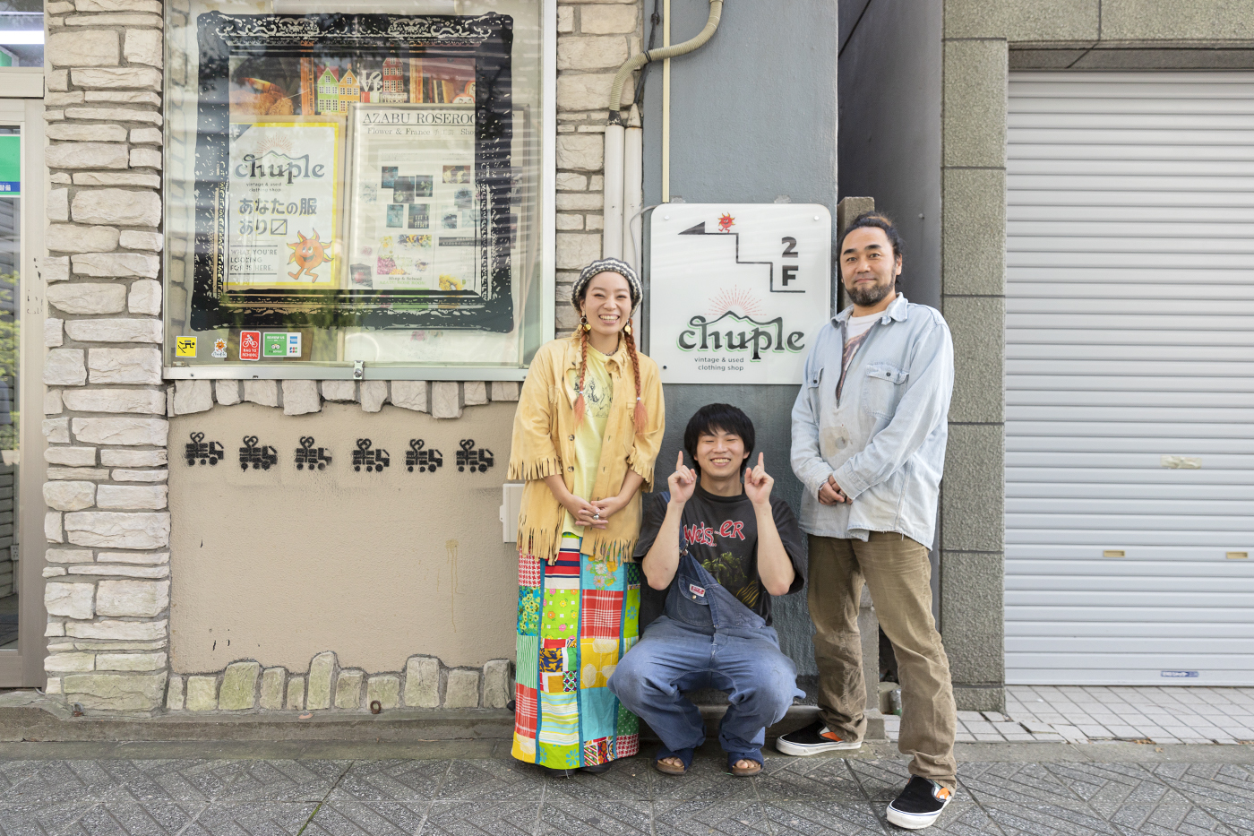 古着屋「chuple」の看板前で学生ライターの八嶋くんを囲みポーズをとるメグミさんとカツゲンさん