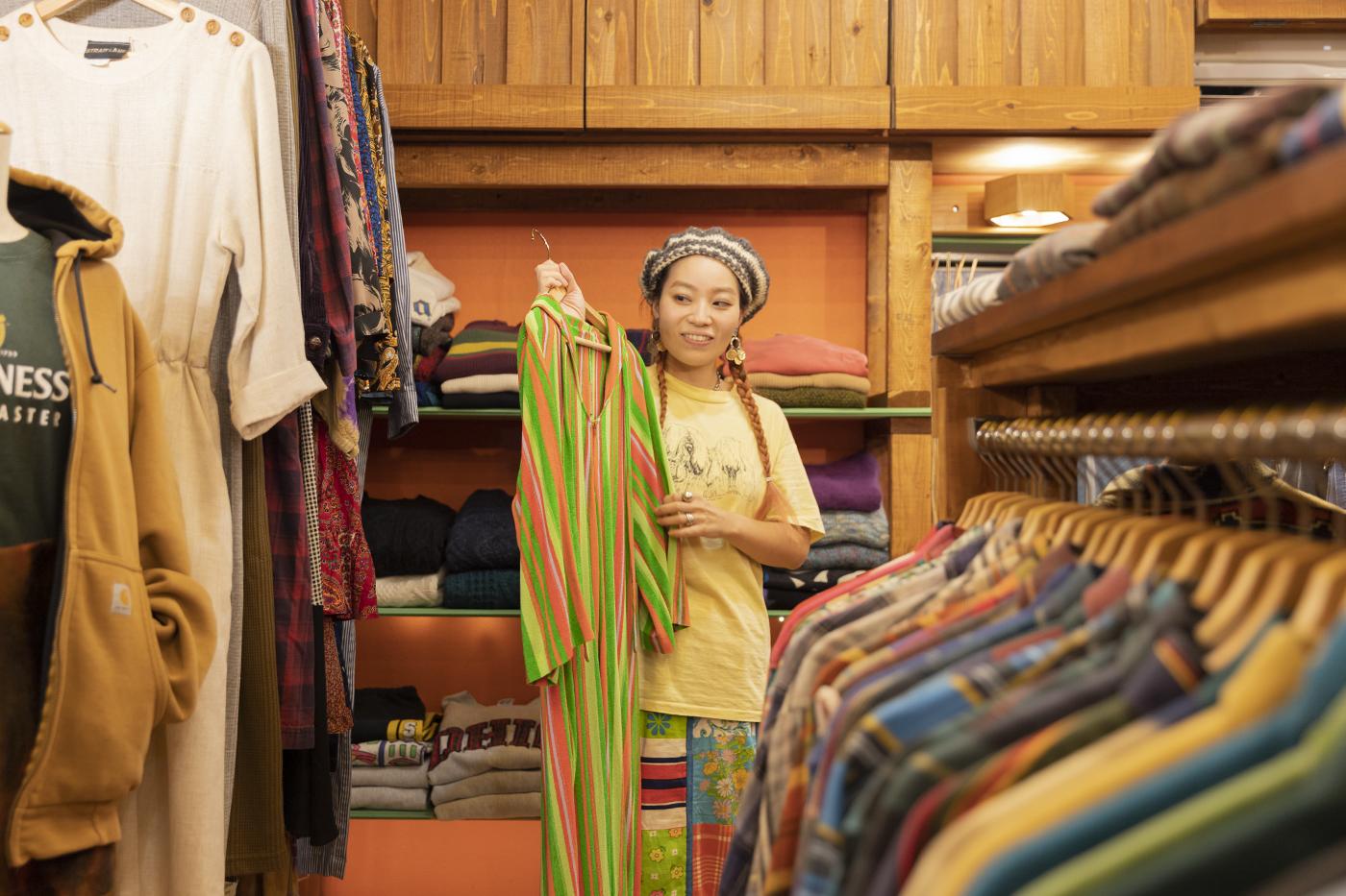 古着屋「chuple」内で色鮮やかなストライプのワンピースを持つメグミさん