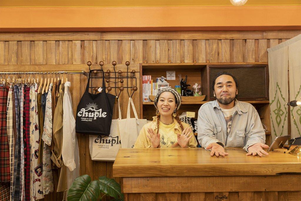 古着屋「chuple」のカウンターでポーズをとるメグミさんとカツゲンさん。後ろには「chuple」オリジナルのロゴトートバックがか見える