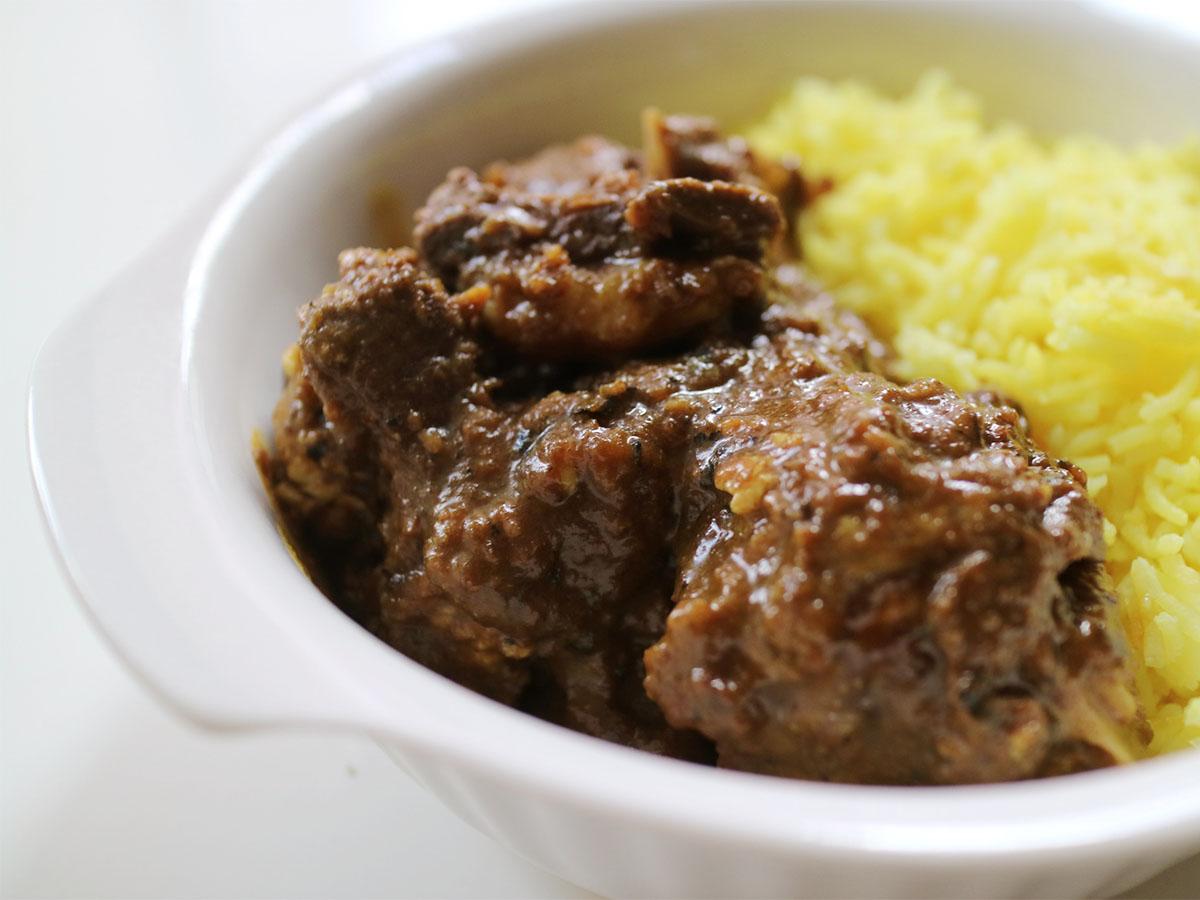 「旨味凝縮マトンカレー」のアップの写真。大きなマトンの肉にサフランライスが盛られている
