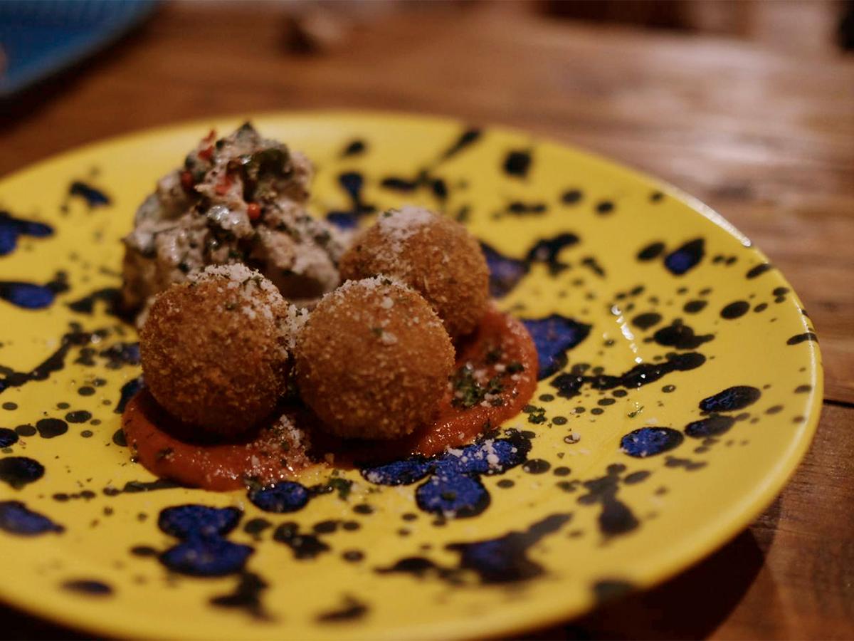 「ツバメ.フード」のライスコロッケ。まん丸のコロッケが黄色い皿に盛りつけられている