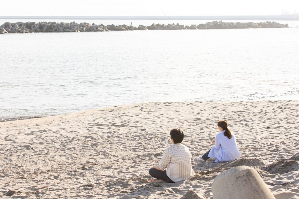 NHKドラマ「あなたのそばで明日が笑う」主演の綾瀬はるかと池松壮亮が砂浜に座り込んでいる